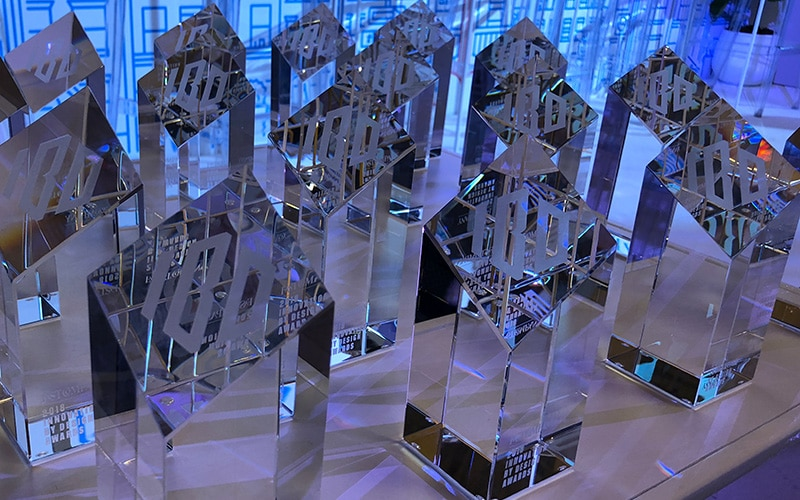 Innovation By Design Award trophies arrayed on a table.