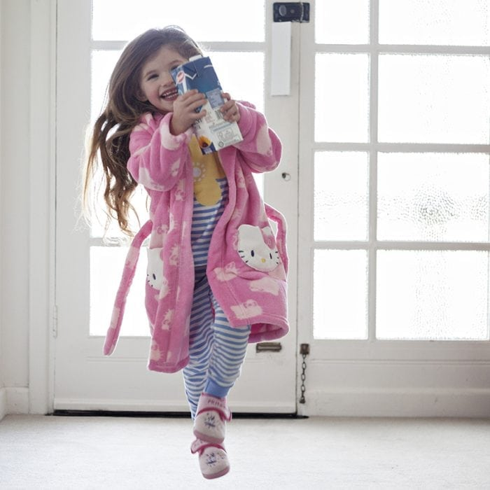 Young girl running indoors with milk carton.