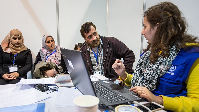 A migrant family in consultation with an IOM aid worker.