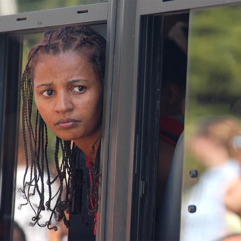 Woman with dreadlocks looking out window of a train.