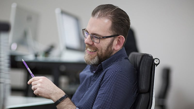 A Frontend.com team member smiling at his desk in the Dublin studio.
